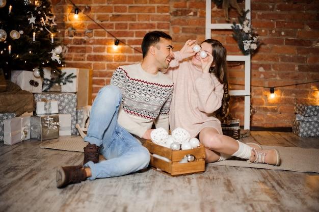 Szczęśliwa kobieta w ciąży z mężem siedzi w pobliżu choinki i pudełka