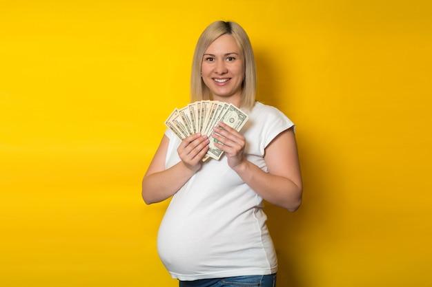 Szczęśliwa kobieta w ciąży z pieniędzmi, dolarów na żółtej ścianie. korzyści dla kobiet w ciąży