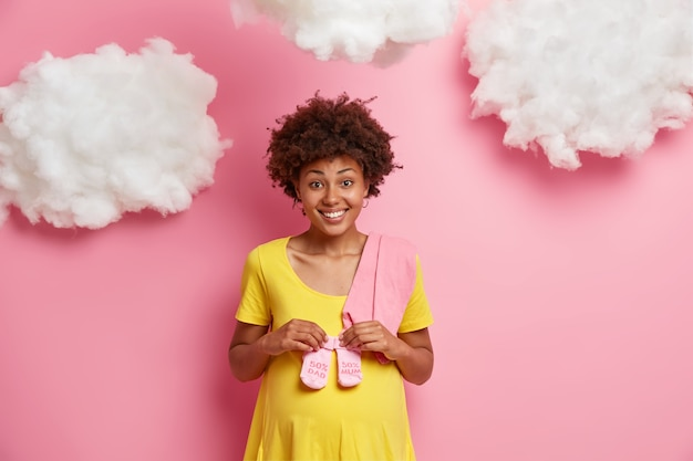 Szczęśliwa kobieta w ciąży z włosami afro trzyma skarpetki na brzuchu przygotowuje się do porodu