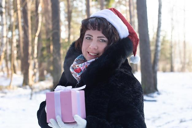 Szczęśliwa kobieta w ciele w naturze w zimie z darem, christma