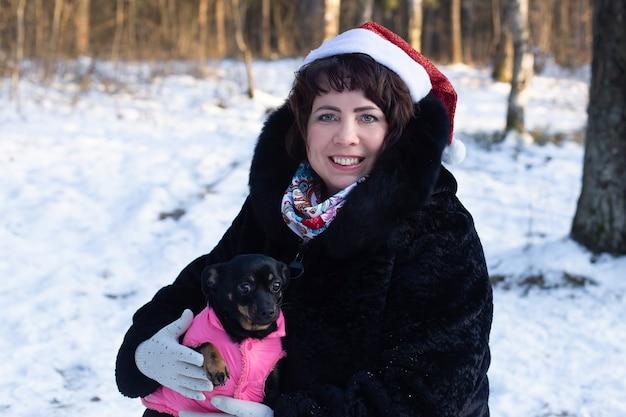 Szczęśliwa kobieta w ciele w przyrodzie zimą z psem, boże narodzenie