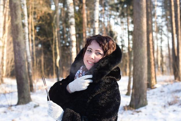 Szczęśliwa kobieta w ciele w przyrodzie zimą z zimnymi ogniami, boże narodzenie
