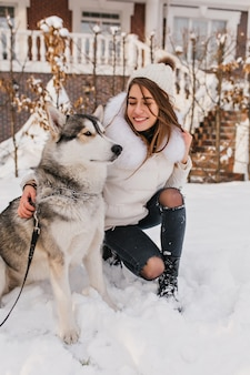 Szczęśliwa kobieta w czarnych dżinsach siedzi na śniegu po zabawnej grze z husky. zewnątrz portret chilling europejskiej kobiety z psem w weekend grudnia.