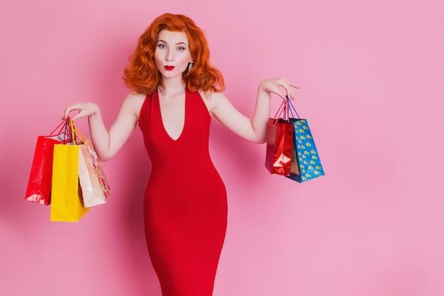 Szczęśliwa kobieta w czerwieni sukni z torba na zakupy na różowym tle.