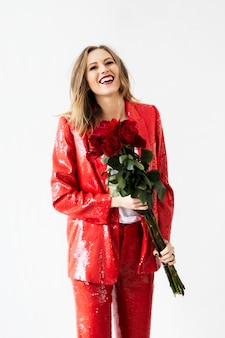 Szczęśliwa kobieta w czerwonym dresie z bukietem róż