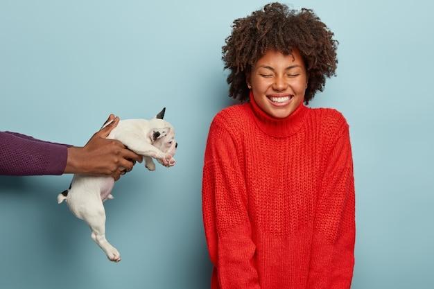 Szczęśliwa kobieta w czerwonym swetrze otrzymującym szczeniaka