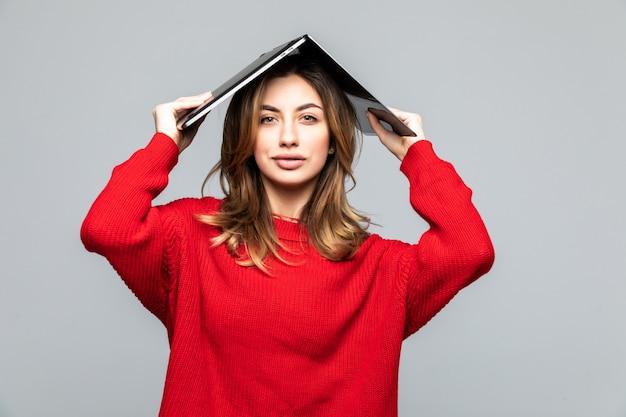 Szczęśliwa kobieta w czerwonym swetrze, trzymając laptopa nad głową jak dach nad szarą ścianą.