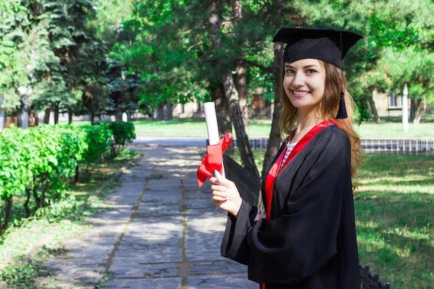 Szczęśliwa kobieta w dniu jej ukończenia. uniwersytet, edukacja i szczęśliwi ludzie