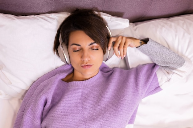 Szczęśliwa kobieta w domu na wygodnym łóżku, ubrana w ciepły sweter, słuchaj muzyki