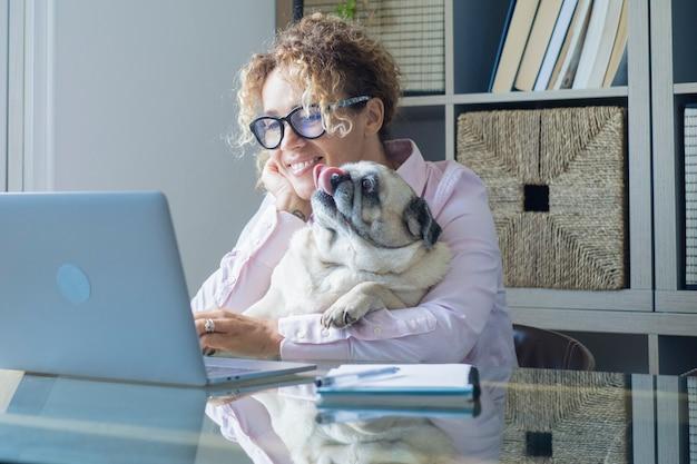 Szczęśliwa kobieta w domu w miłości do swojego najlepszego przyjaciela mopsa podczas pracy na komputerze przenośnym na pulpicie
