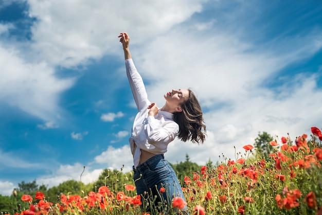 Szczęśliwa kobieta w dorywczo tkaniny na polu maków cieszyć się wolnym czasem letnim. natura