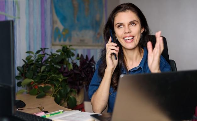 Szczęśliwa kobieta w dżinsowej koszuli pracującej w domu z laptopem