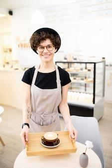 Szczęśliwa kobieta w fartuchu pracuje w sklep z kawą