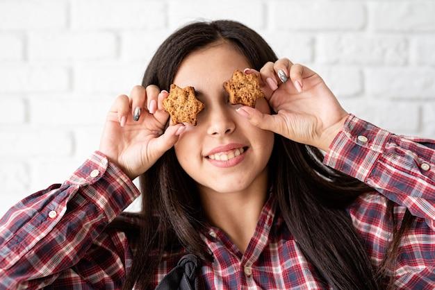 Szczęśliwa kobieta w fartuchu, trzymając ciasteczka w kształcie gwiazdy przed oczami