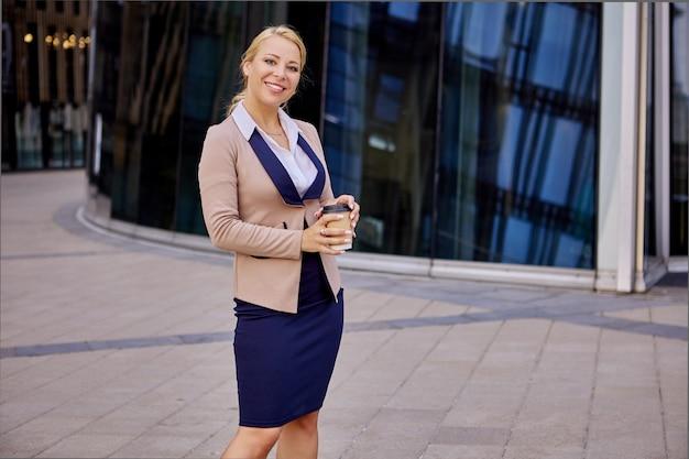 Szczęśliwa kobieta w garniturze stoi w pobliżu centrum biznesowego z kawą na wynos