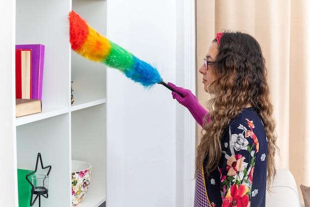 Szczęśliwa kobieta w gumowych rękawiczkach czyści półki za pomocą statycznej miotełki w domu w jasnym salonie