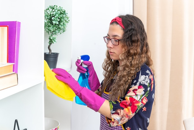 Szczęśliwa kobieta w gumowych rękawiczkach wyciera białe półki żółtą szmatką za pomocą sprayu do czyszczenia w domu w jasnym salonie