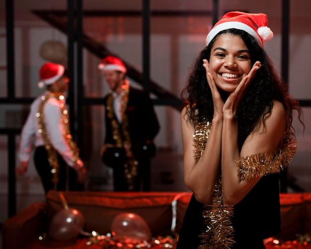 Szczęśliwa kobieta w kapeluszu santa na imprezie sylwestrowej