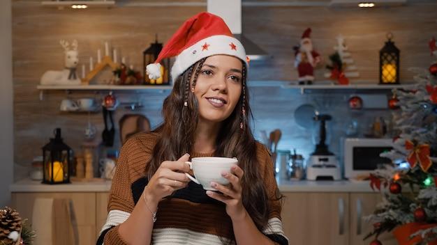 Szczęśliwa kobieta w kapeluszu świętego mikołaja myśląca o czasie świątecznym