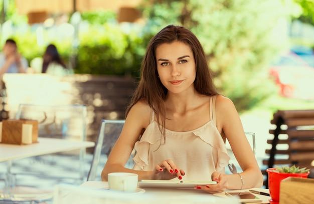 Szczęśliwa kobieta w kawiarni na świeżym powietrzu