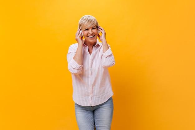 Szczęśliwa kobieta w koszuli i dżinsach słucha muzyki w słuchawkach