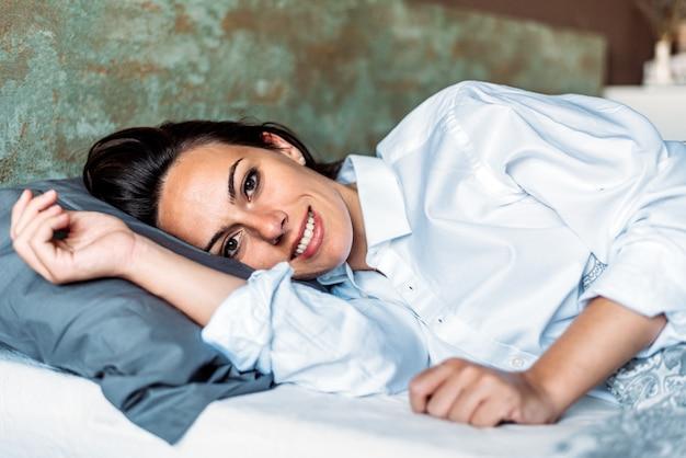 Szczęśliwa kobieta w koszuli leżąc w łóżku