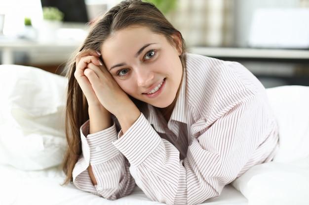 Szczęśliwa kobieta w koszuli mans leży na łóżku