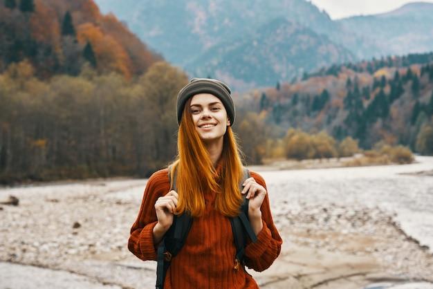 Szczęśliwa kobieta w lesie jesienią w górach na świeżym powietrzu z plecakiem na plecach turystyka podróżnicza. wysokiej jakości zdjęcie