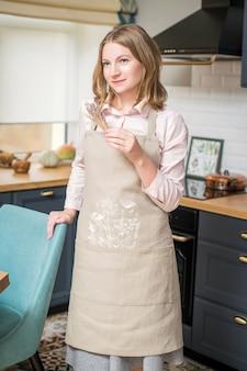 Szczęśliwa kobieta w lnianym fartuchu stoi w kuchni i trzyma w rękach suchy bukiet lawendy