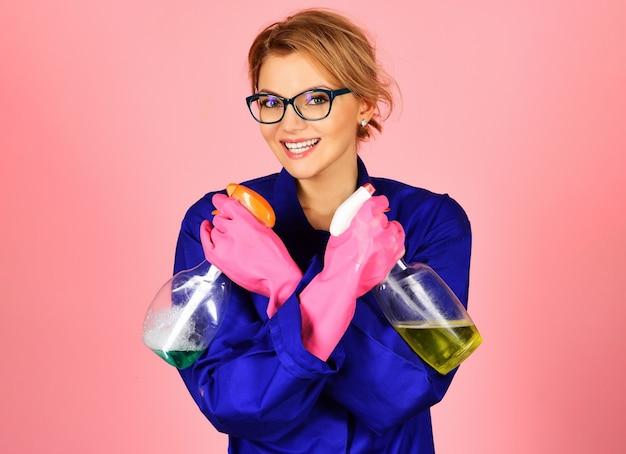 Szczęśliwa kobieta w mundurach i gumowych rękawiczkach z sprayem do czyszczenia. profesjonalna usługa sprzątania.