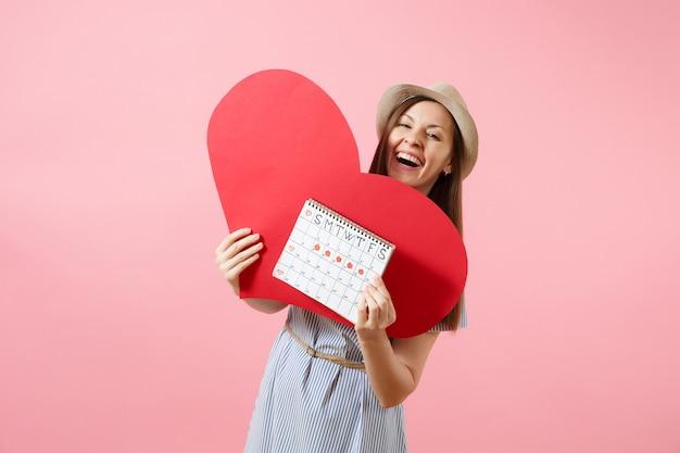 Szczęśliwa kobieta w niebieskiej sukience kapelusz lato gospodarstwa puste puste duże czerwone serce, kalendarz kobiet okresów, sprawdzanie dni menstruacji na białym tle. medyczna koncepcja ginekologiczna opieki zdrowotnej. skopiuj miejsce
