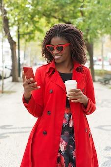 Szczęśliwa kobieta w okularach przeciwsłonecznych używać smartphone