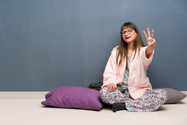 Szczęśliwa kobieta w piżamie na podłodze i licząc trzy palcami