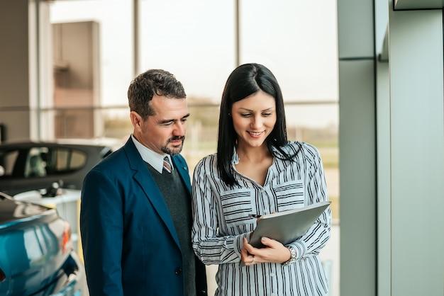 Szczęśliwa kobieta w przedstawicielstwie firmy samochodowej pokazuje dokumenty klient.