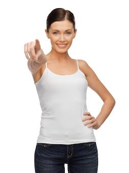 Szczęśliwa kobieta w pustym białym t-shircie wskazując palcem