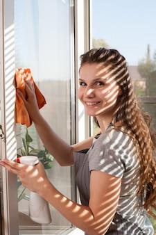Szczęśliwa kobieta w rękawice czyszczenia okna z szmatką i sprayem do mycia w domu