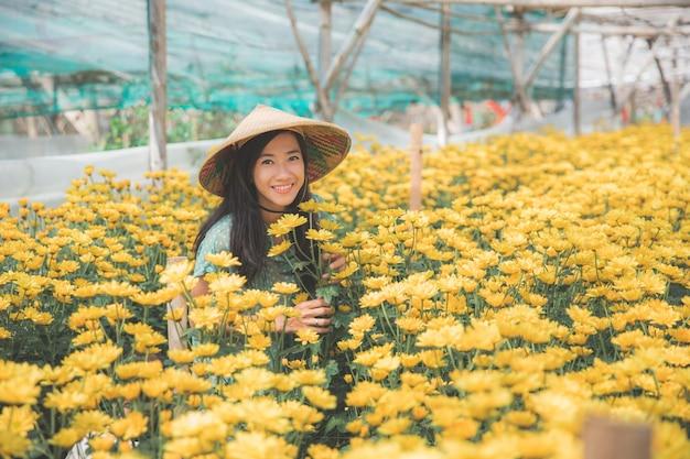 Szczęśliwa kobieta w rumianku gospodarstwie rolnym