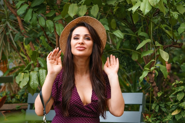 Szczęśliwa kobieta w słomkowym kapeluszu siedzi na ławce w parku
