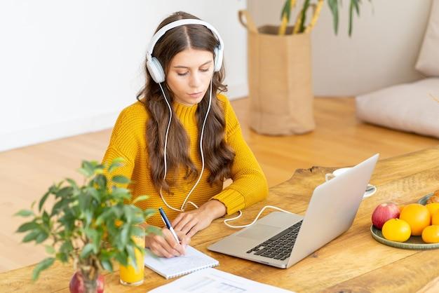 Szczęśliwa kobieta w słuchawkach bezprzewodowych studiująca kurs online, używając komputera i pisania w notatniku, miejsce na kopię