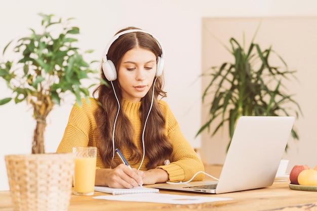 Szczęśliwa kobieta w słuchawkach bezprzewodowych uczy się kursu online, używa komputera i pisze w notatniku