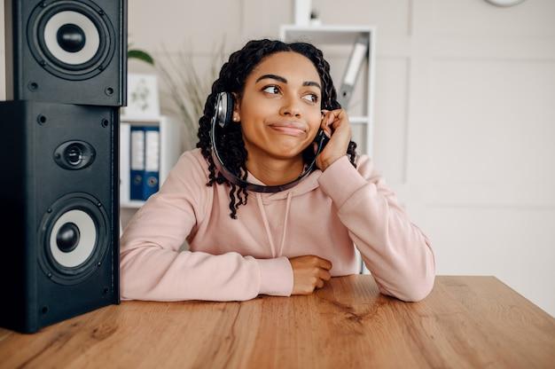 Szczęśliwa kobieta w słuchawkach siedzi w pobliżu głośnika i słuchanie muzyki. ładna pani odpoczywa w pokoju, a miłośniczka dźwięków odpoczywa