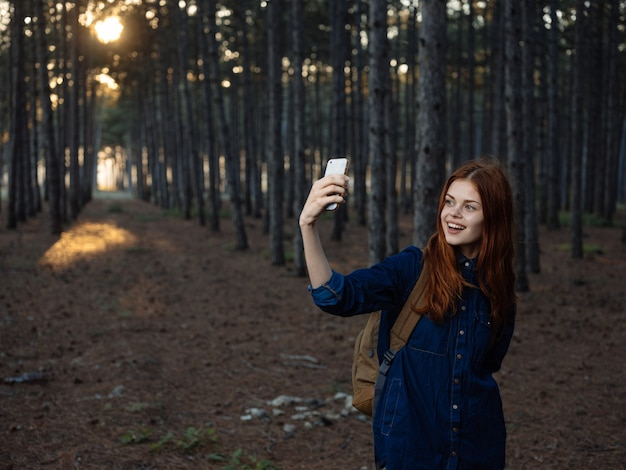 Szczęśliwa kobieta w sosnowym lesie z modelem turystyki nawigatora telefonu komórkowego