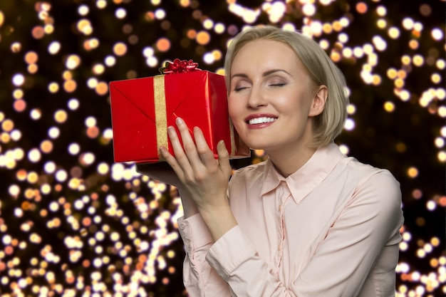 Szczęśliwa kobieta w średnim wieku cieszy się swoim prezentem