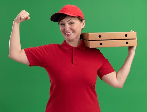 Szczęśliwa kobieta w średnim wieku dostawy w czerwonym mundurze i czapce, trzymając pudełka po pizzy, podnosząc pięść, patrząc na przód, uśmiechając się pewnie stojąc nad zieloną ścianą