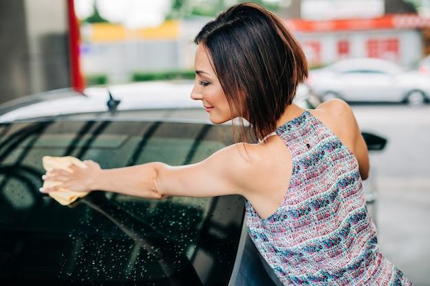 Szczęśliwa kobieta w średnim wieku mycie samochodu wieczorem na myjni samochodowej.