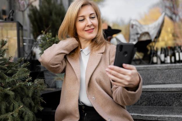 Szczęśliwa kobieta w średnim wieku, sprawdzanie swojego telefonu