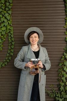 Szczęśliwa kobieta w średnim wieku trzyma aparat