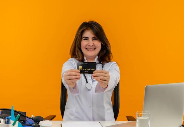 Szczęśliwa kobieta w średnim wieku ubrana w szlafrok medyczny i stetoskop siedzi przy biurku ze schowkiem na narzędzia medyczne i laptopem wyciągając kartę kredytową na białym tle