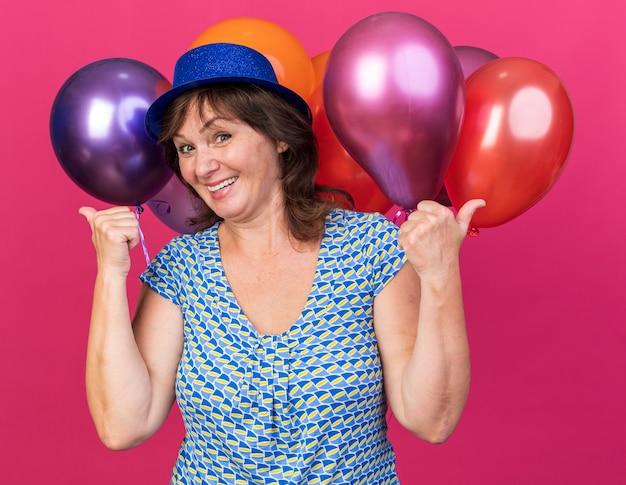 Szczęśliwa kobieta w średnim wieku w imprezowym kapeluszu trzyma kolorowe balony, uśmiechając się radośnie pokazując kciuki w górę