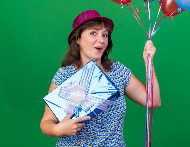 Szczęśliwa kobieta w średnim wieku w imprezowym kapeluszu trzymająca kolorowe balony i prezentująca uśmiechnięta radośnie świętująca przyjęcie urodzinowe stojąca nad zieloną ścianą